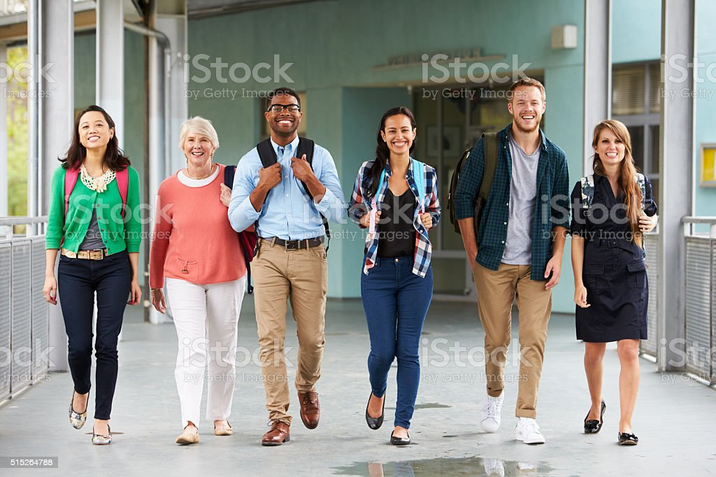A group of happy teachers walking in a school corridor stock photo