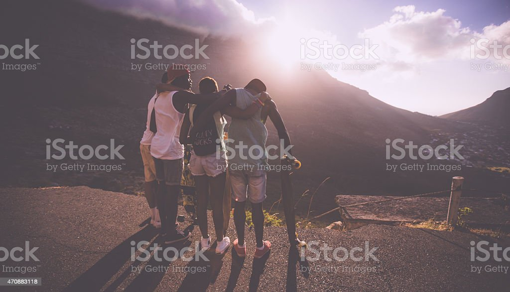 Group of happy teen friends standing together with longboards stock photo
