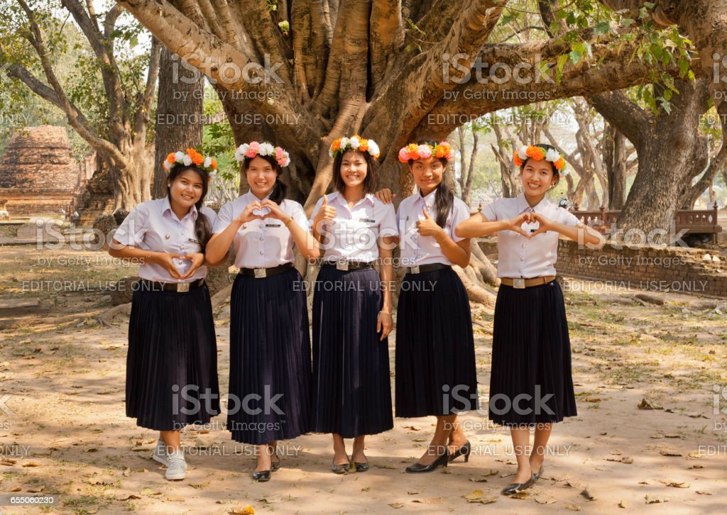 Group of happy Thai girls with flower wreath invite guests to visit the country stock photo