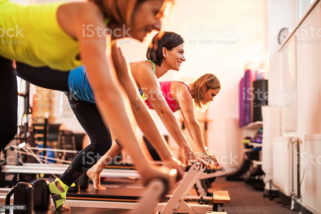 Group of happy women exercising on Pilates training class. stock photo