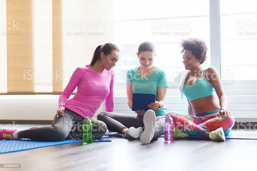 group of happy women with tablet pc in gym stock photo