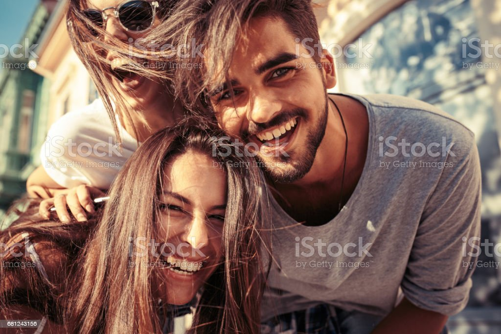 Group of happy young friends having fun on city street. stock photo