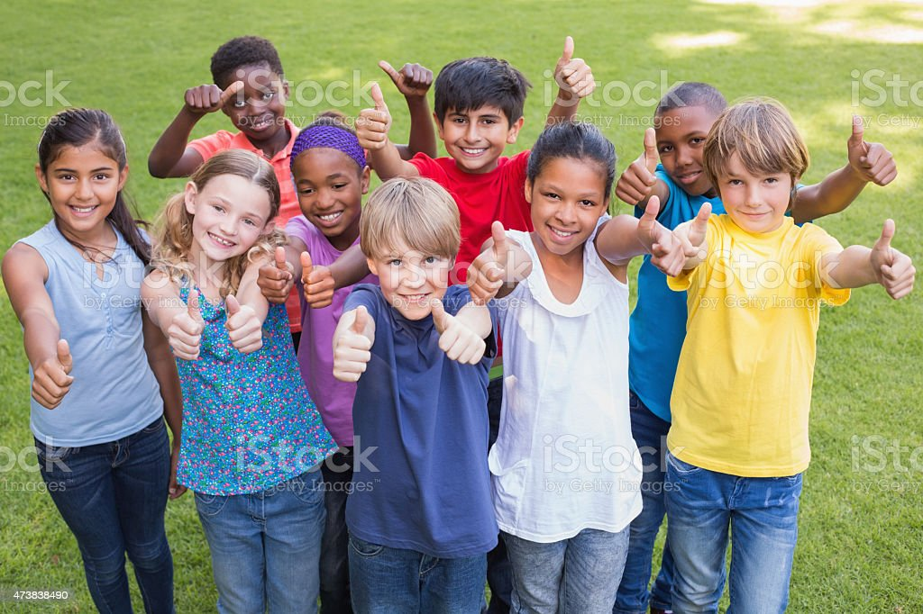 Group of happy young friends with thumbs up in the park stock photo