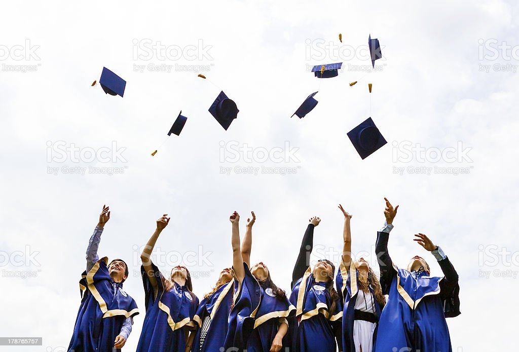 Group of happy young graduates throwing hats stock photo