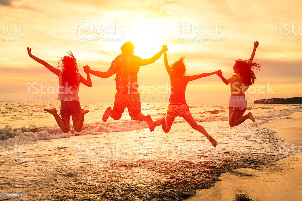 group of happy young people jumping on the beach stock photo