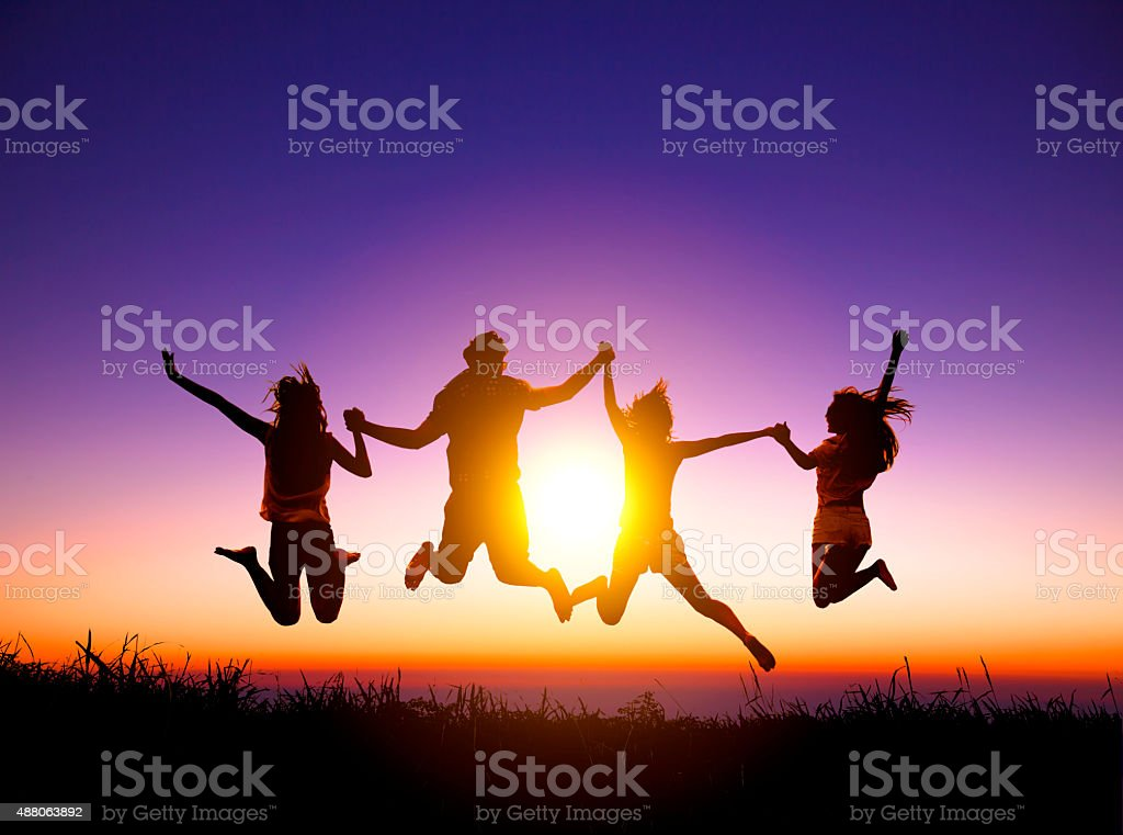 group of happy young people jumping on the mountain stock photo