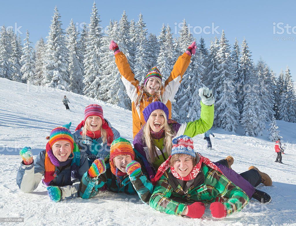 Group of happy young people lying down in ski area royalty-free stock photo
