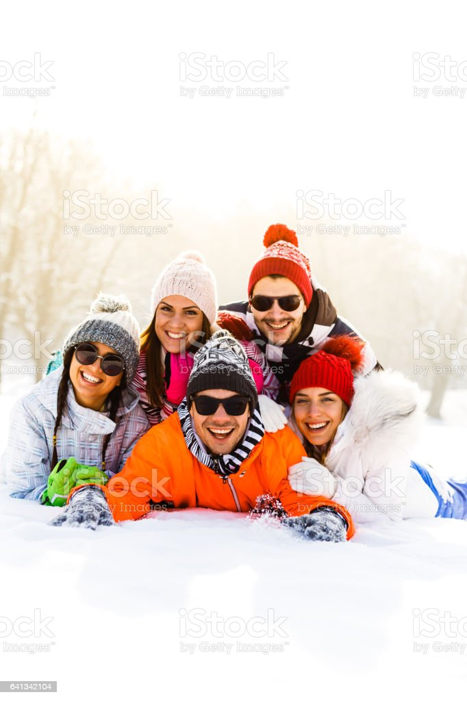 Group of happy young people lying in snow stock photo