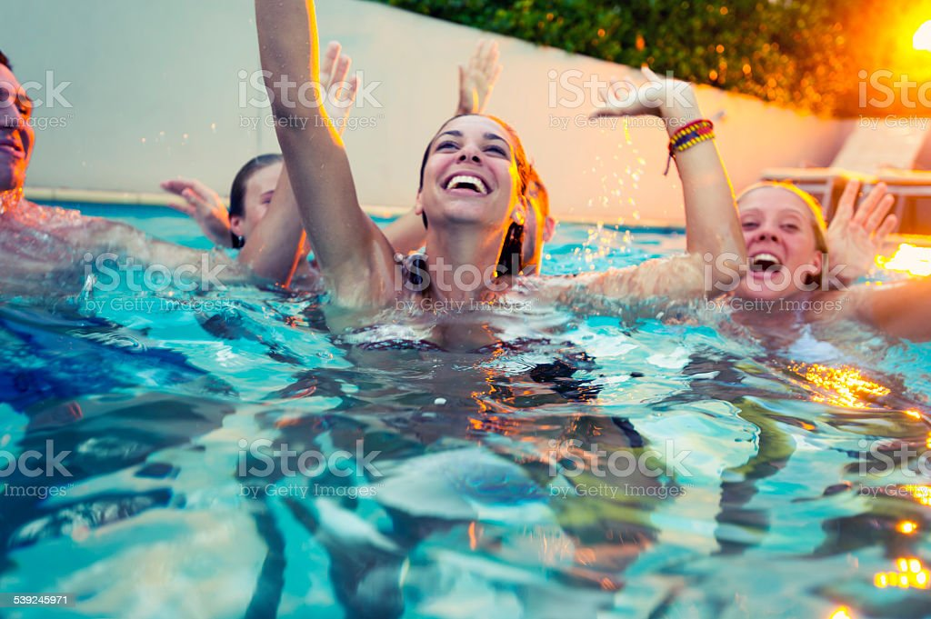 Group of happy young people partying in a pool. stock photo