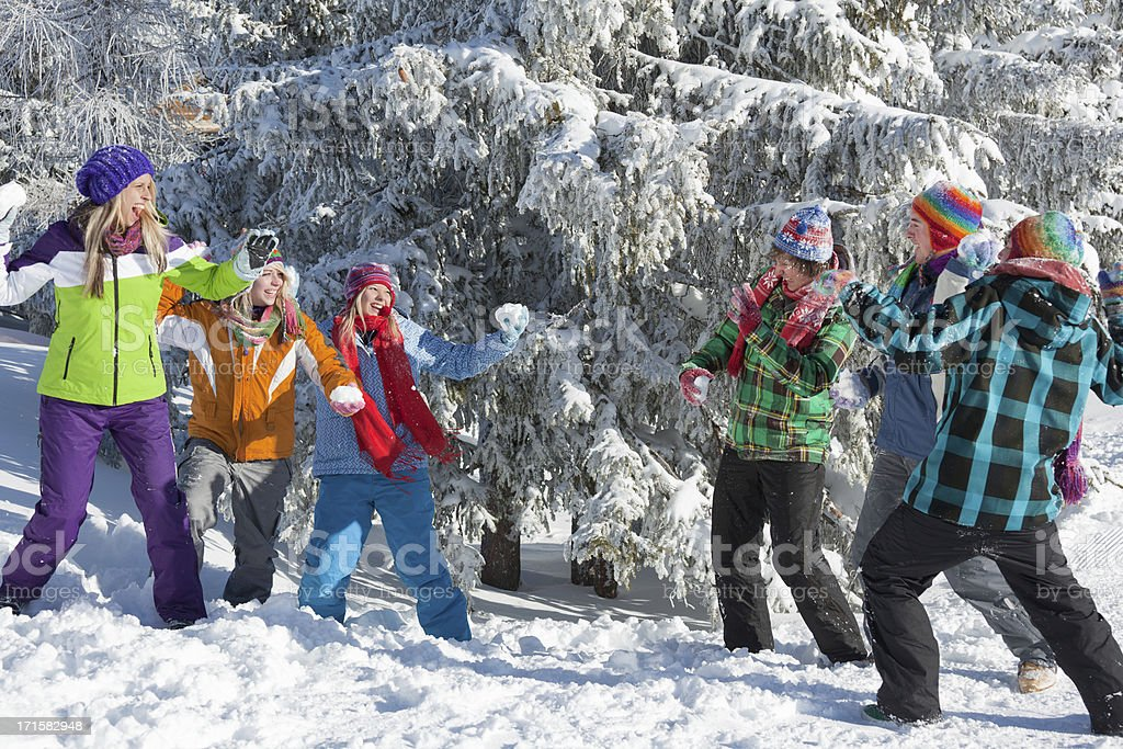 Group of happy young people throwing snowballs royalty-free stock photo