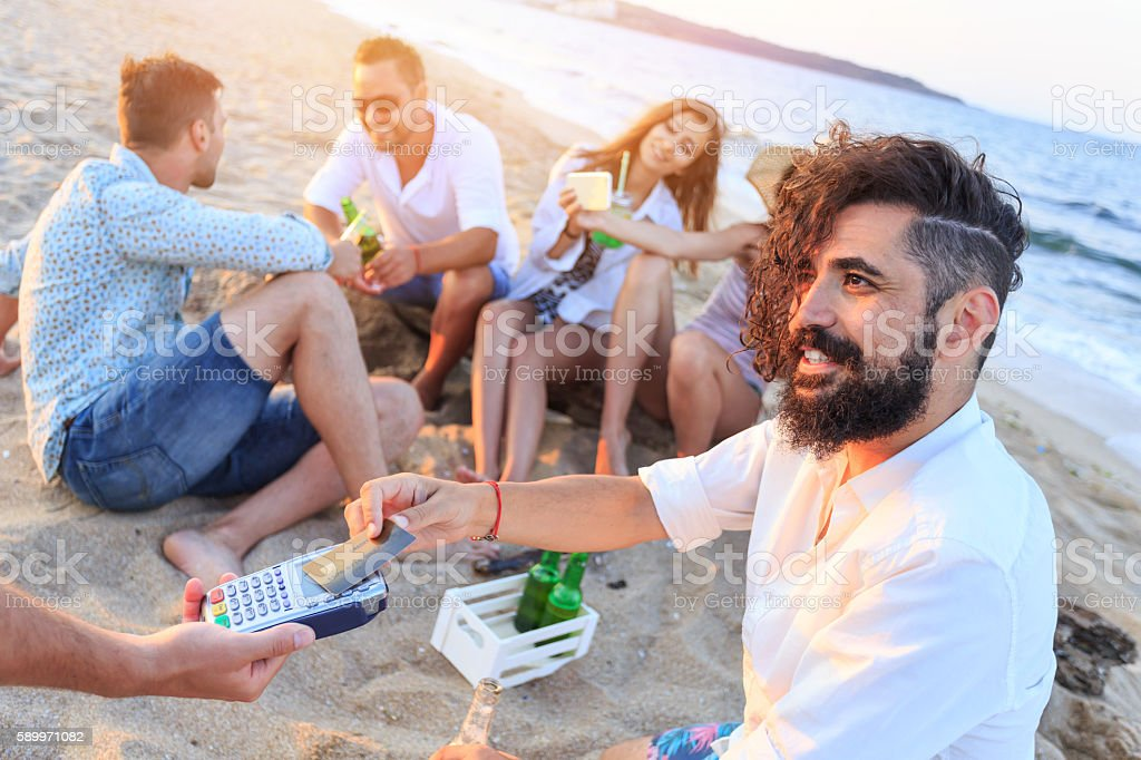 Group of happy young people using credit card on beach stock photo