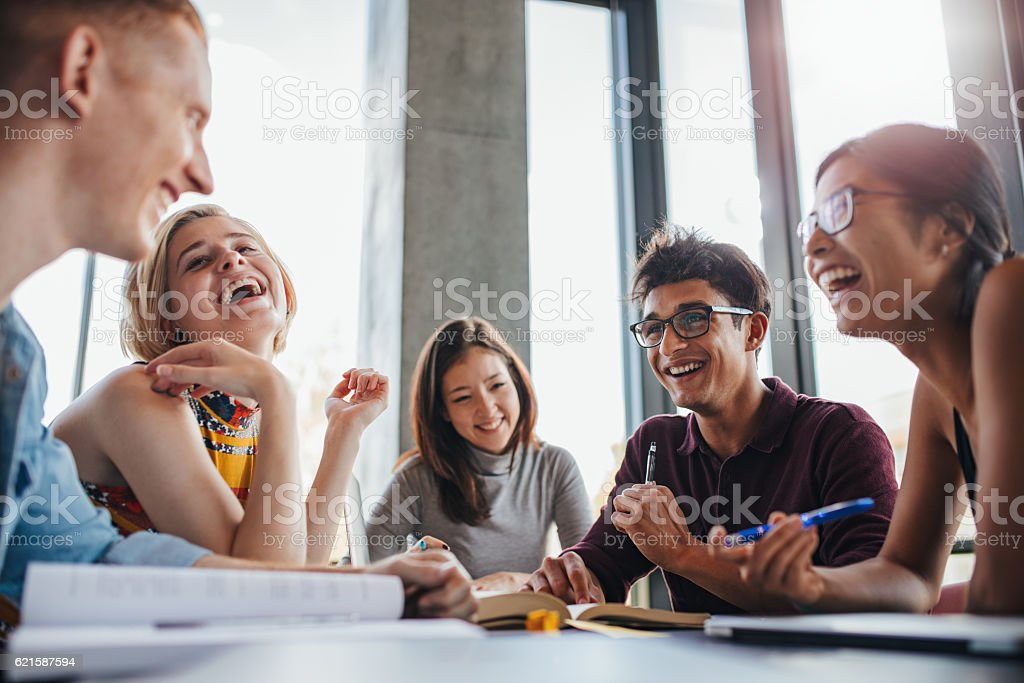 Group of happy young students in library stock photo