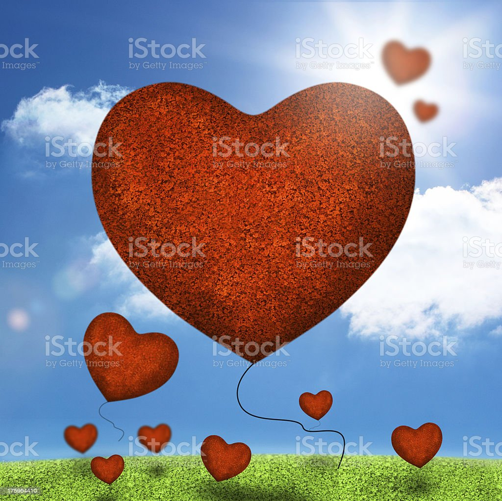 Group of heart balloons floating over field royalty-free stock photo