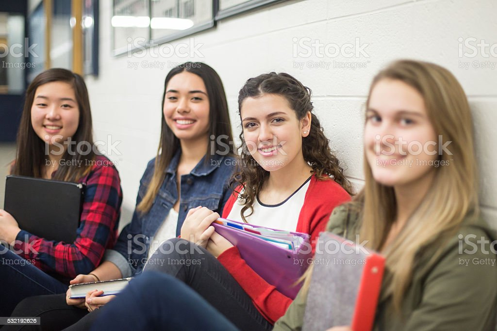 Group of high school girls posing and smiling inside school building stock photo