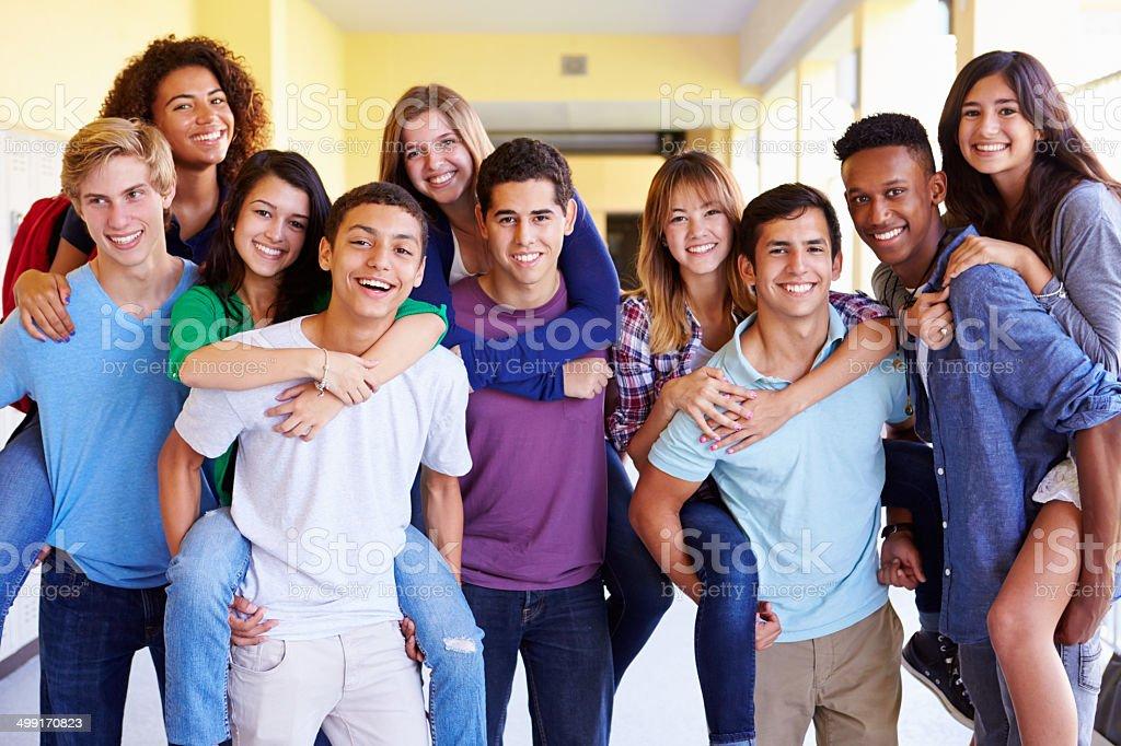 Group Of High School Students Giving Piggybacks In Corridor stock photo