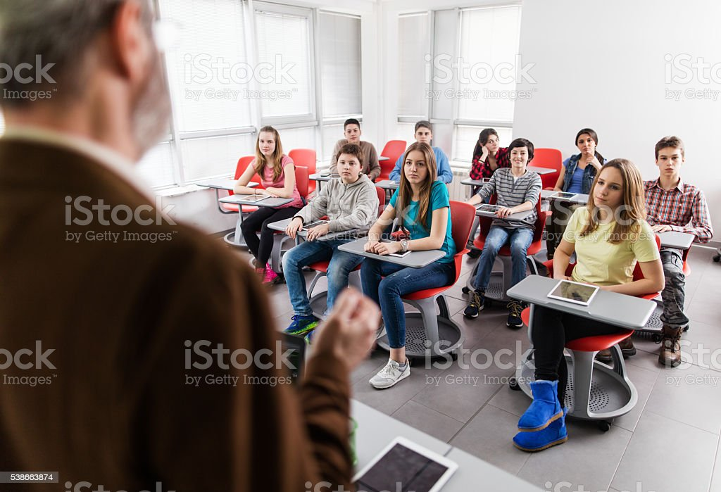 Group of high school students listening to their teacher talking. stock photo