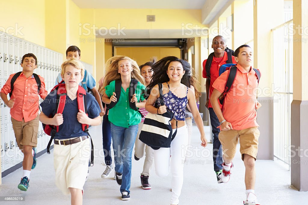 Group Of High School Students Running Along Corridor stock photo