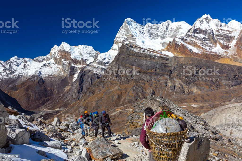 Group of Hikers and Nepalese Porter carrying many camping luggage stock photo