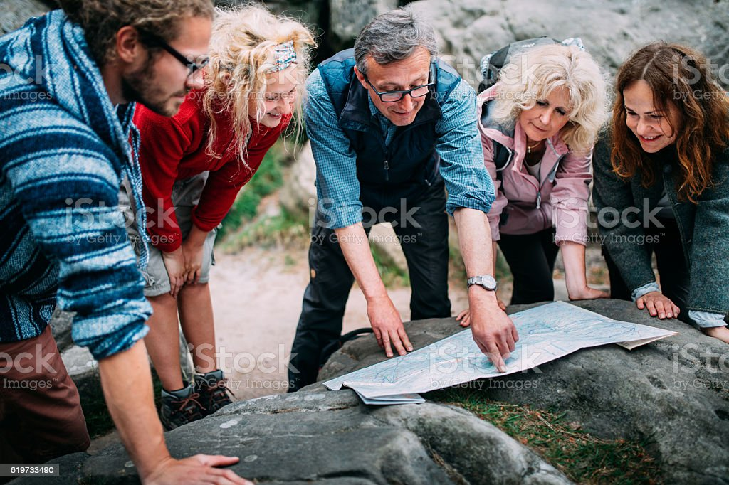 Group of Hikers checking route on map stock photo