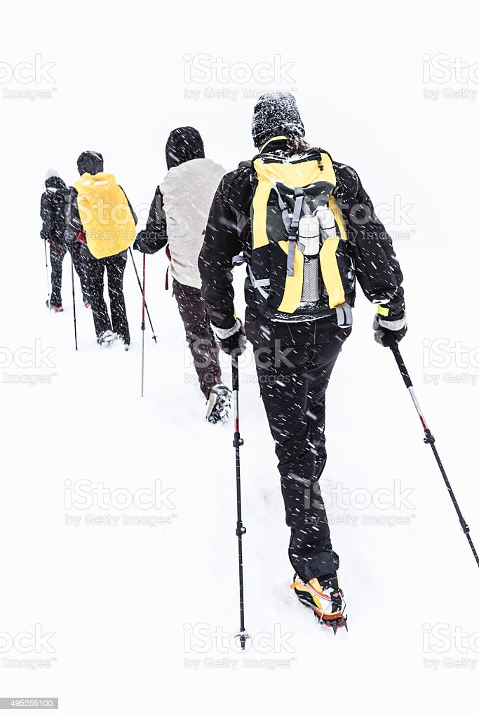 Group of hikers walking on snow-covered mountain stock photo
