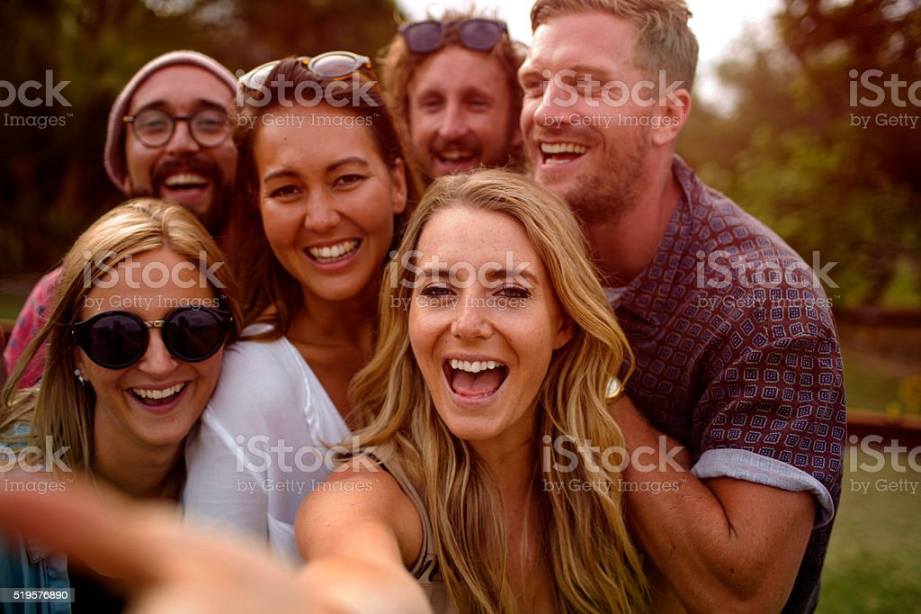 Group of hipster friends taking selfie with stick at sunset stock photo