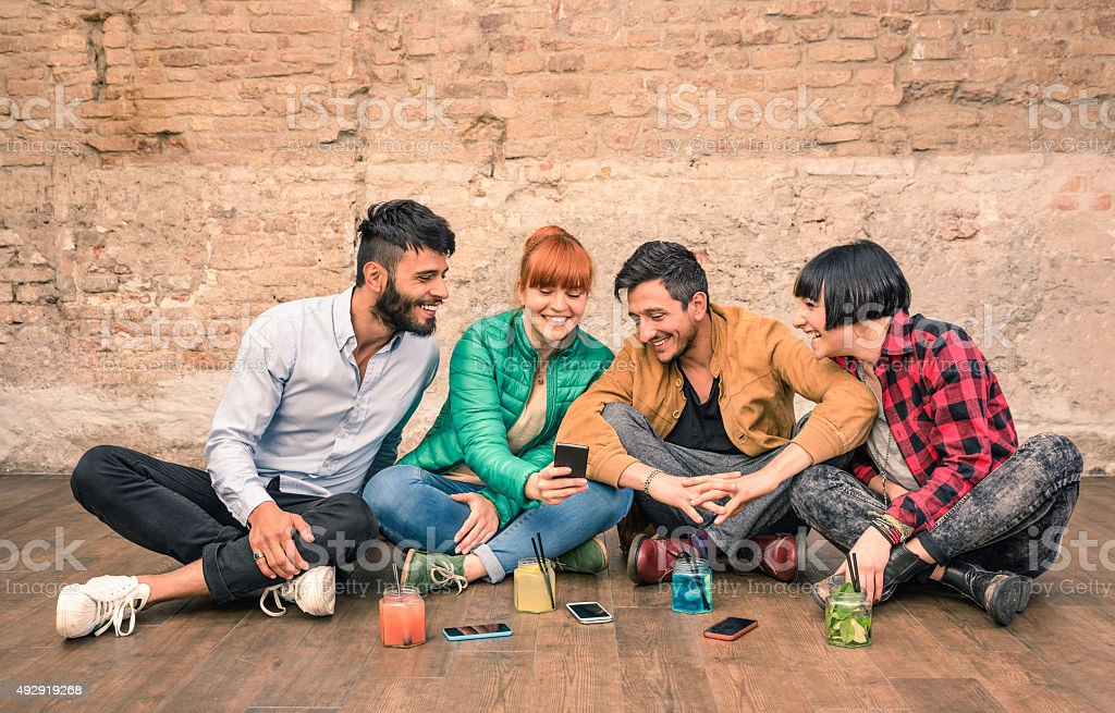 Group of hipster friends with smartphones in grungy alternative location stock photo