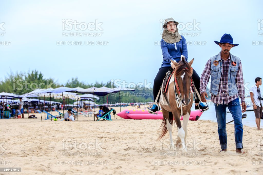 Phetchaburi, Thailand - October 9, 2016: A group of horse riders sitting on a tropical beach. stock photo