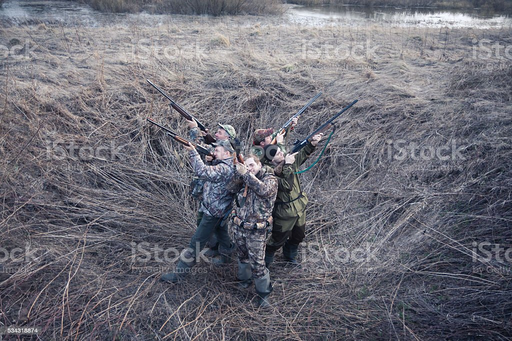 Group of hunters standing back to back in rural field stock photo