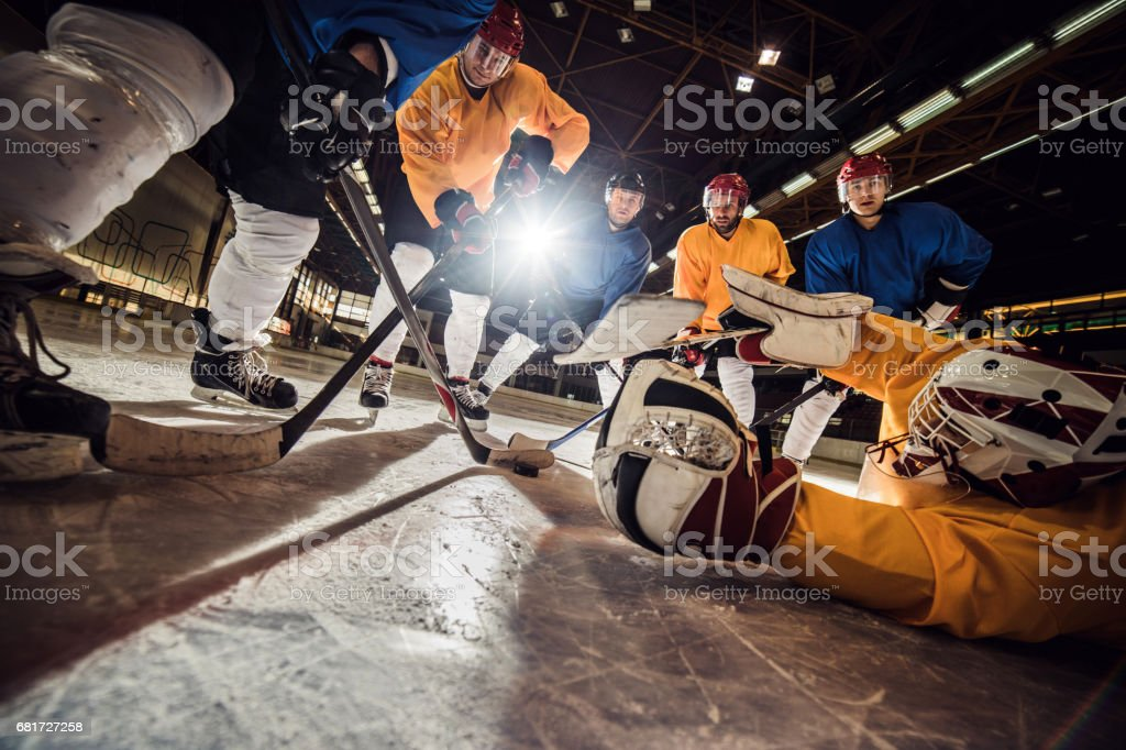 Goalkeeper and ice hockey players in action during the game on ice...