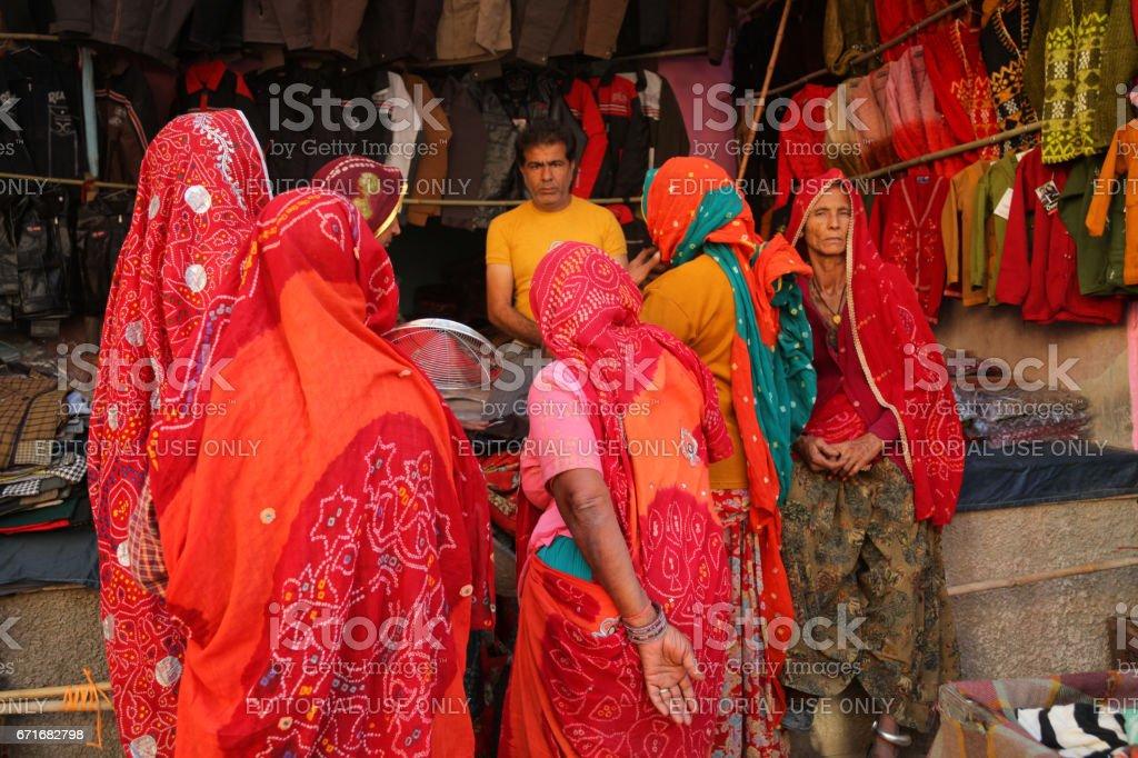 A group of Indian Rural women customers at a clothes stall at Pushkar Camel Fair stock photo