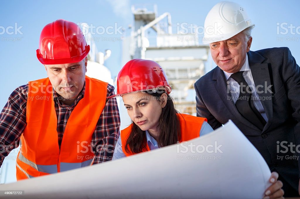Group of industrial engineers analyzing project outdoors stock photo