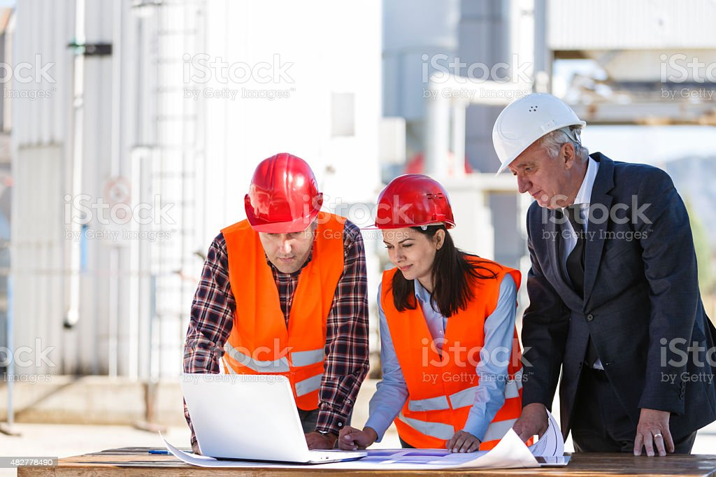 Group of industrial engineers with computer outdoor stock photo