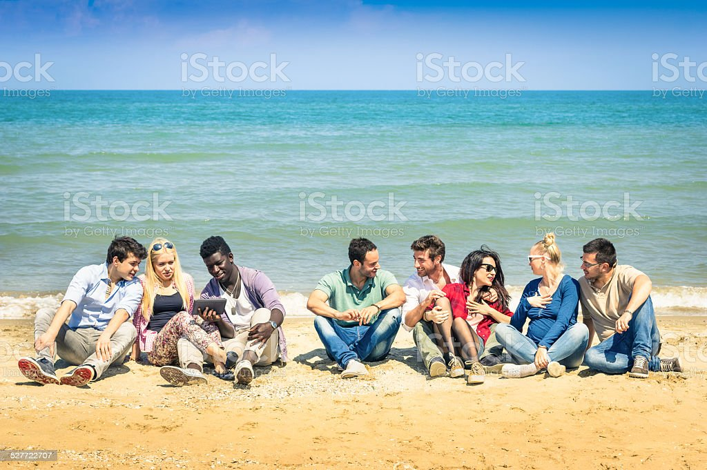 Group of international best friends sitting and talking at beach stock photo