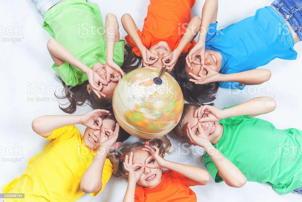 Group of international funny kids with globe earth stock photo