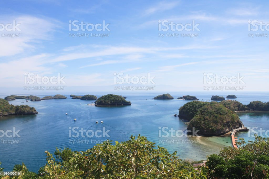Group of islets (small islands) in blue waters with clear blue sky and beautiful trees stock photo