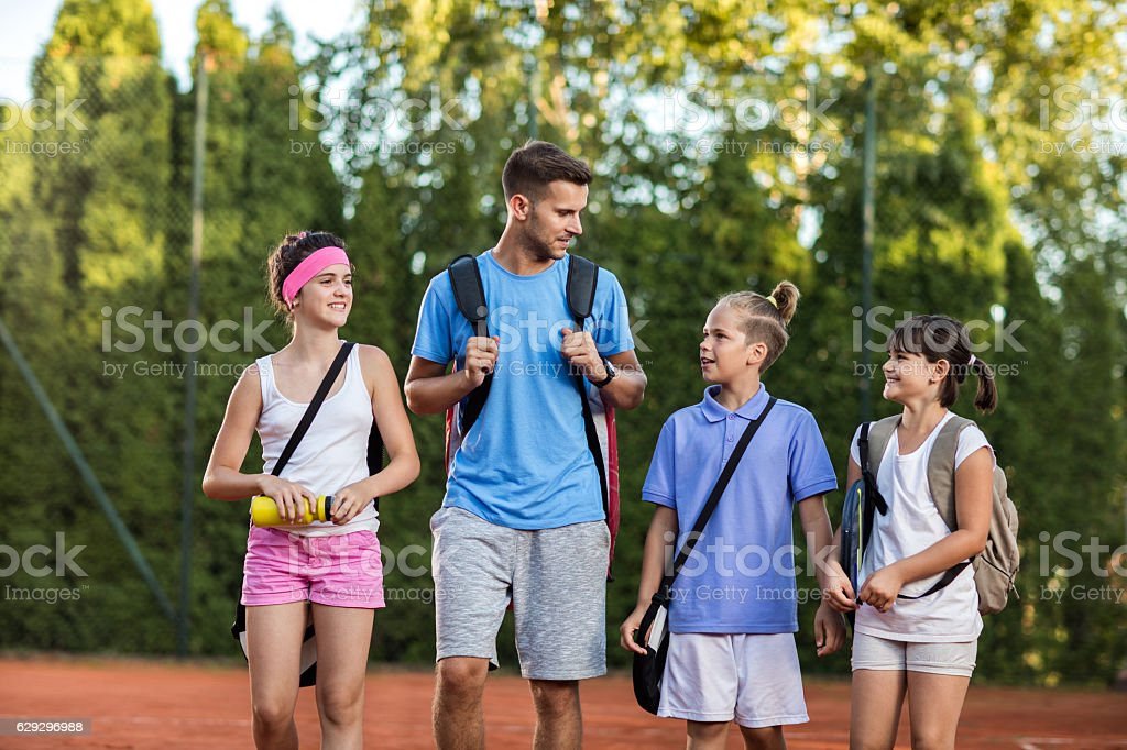 Group of kids and tennis trainer talking after the training. stock photo