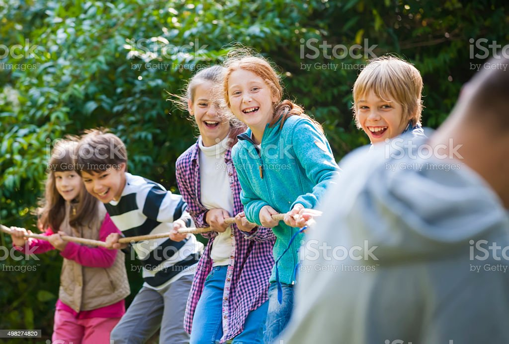 Group of kids in a tug-of-war game stock photo