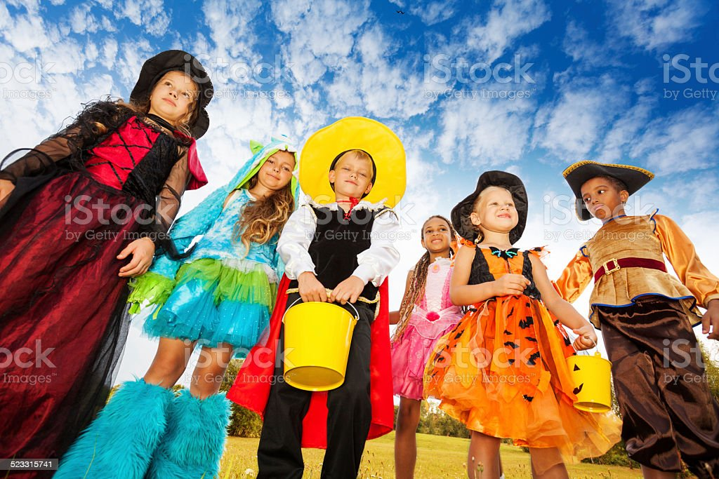 Group of kids in Halloween costumes looks down stock photo