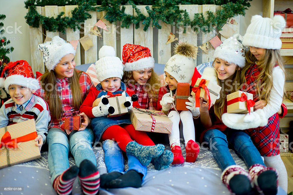 group of kids in red hat with christmas gifts royalty free stock photo