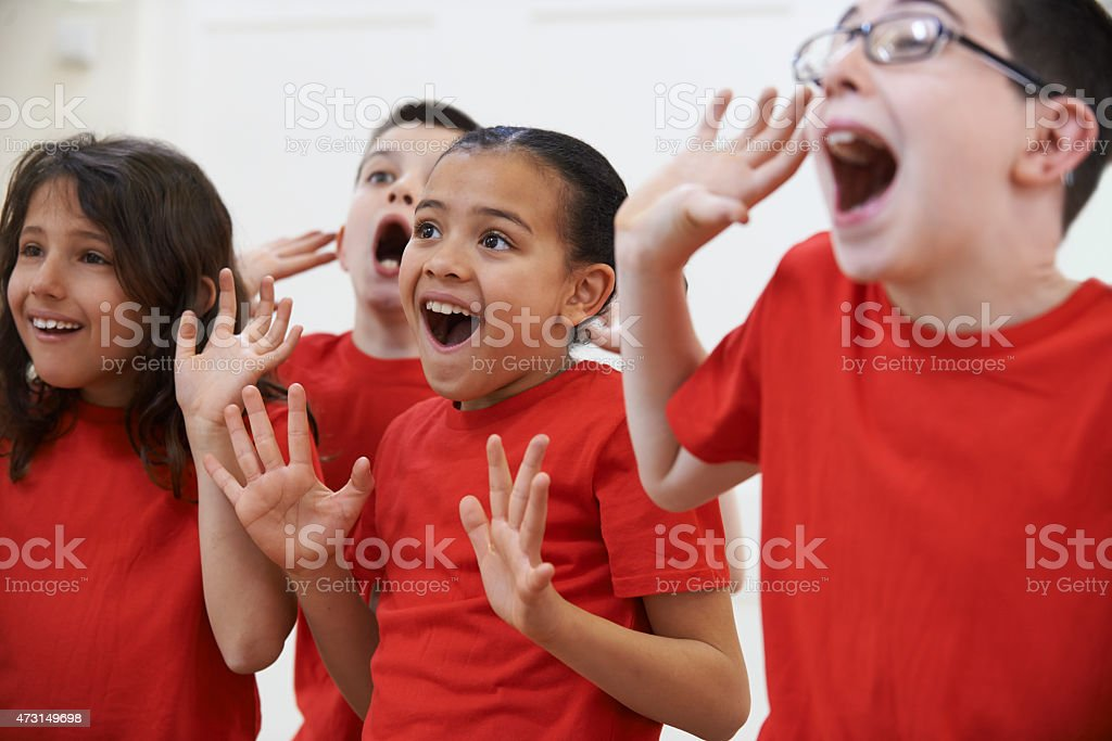 Group of kids in red shirts dramatically acting in drama stock photo