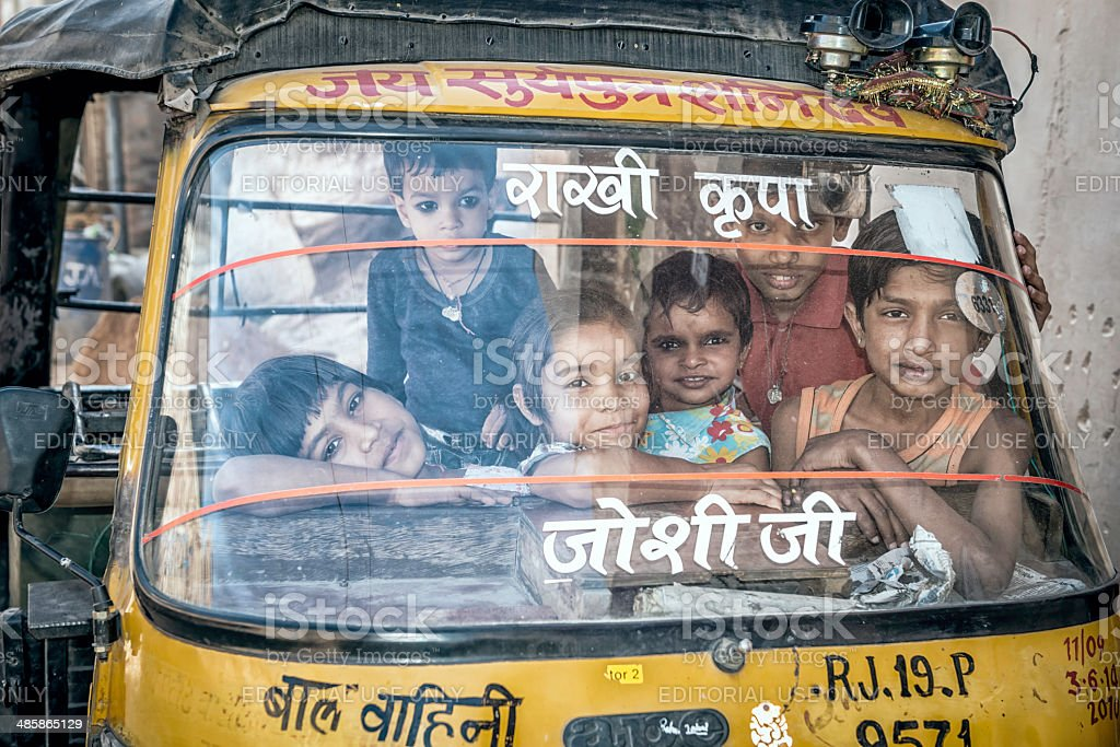 Group of kids playing inside rickshaw in Blue City, Jodhpur. stock photo