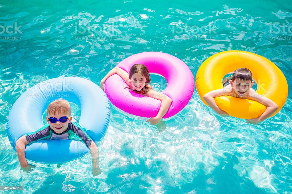 Group of kids playing on inflatable tubes in swimming pool stock photo