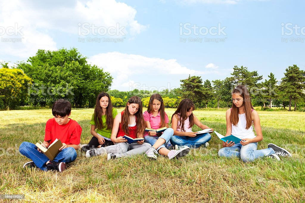 Group Of Kids Reading Books Outdoors royalty-free stock photo