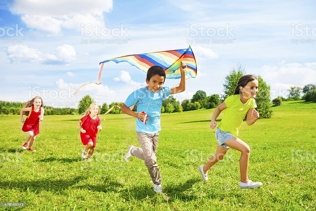 Group of kids run with kite stock photo