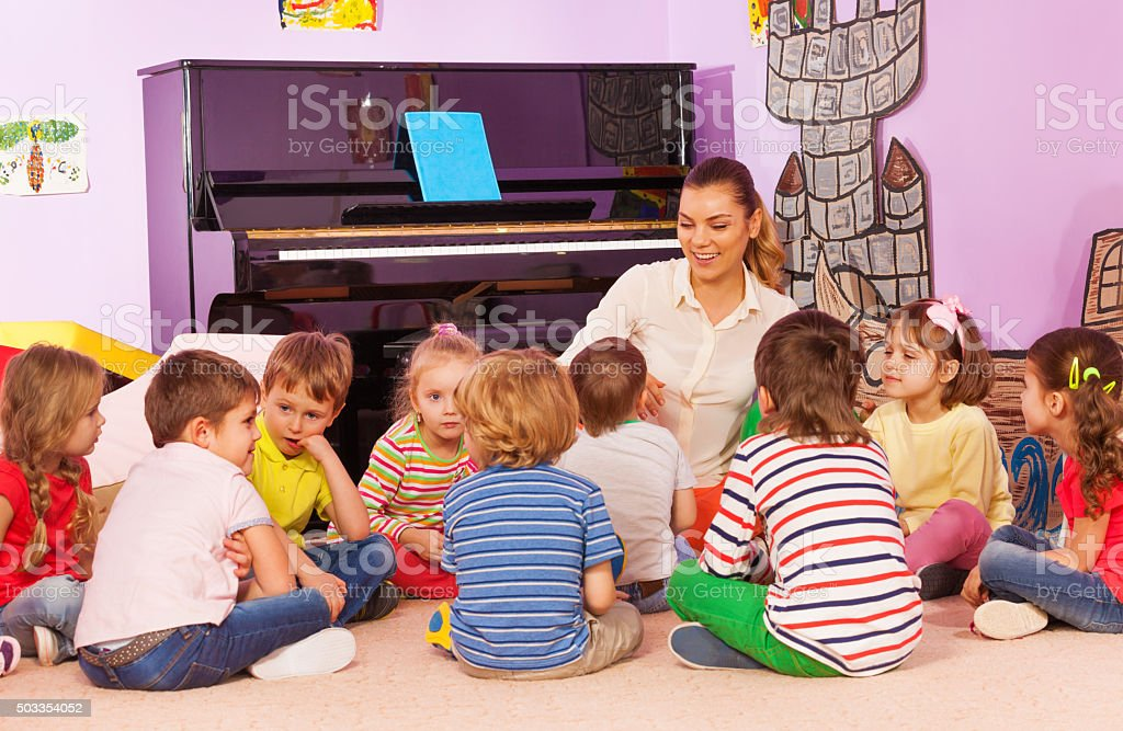 Group of kids sit and listen to teacher tell story stock photo