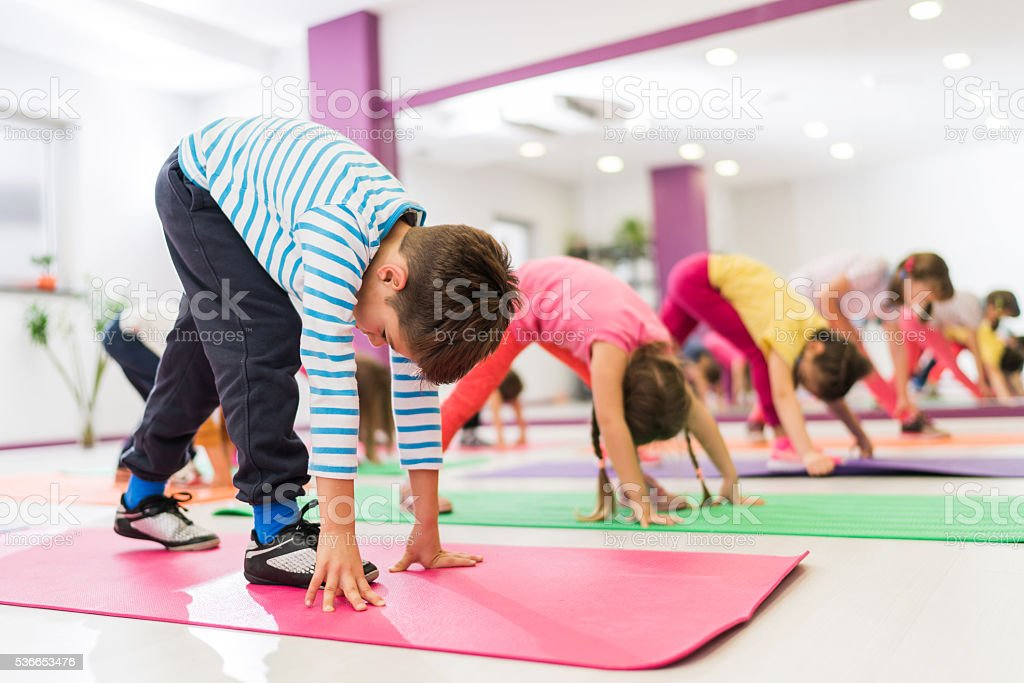 Group of kids stretching their legs on a sports training. stock photo