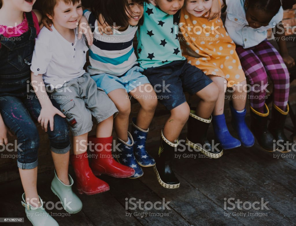 Group of kindergarten kids friends arm around sitting and smiling fun stock photo