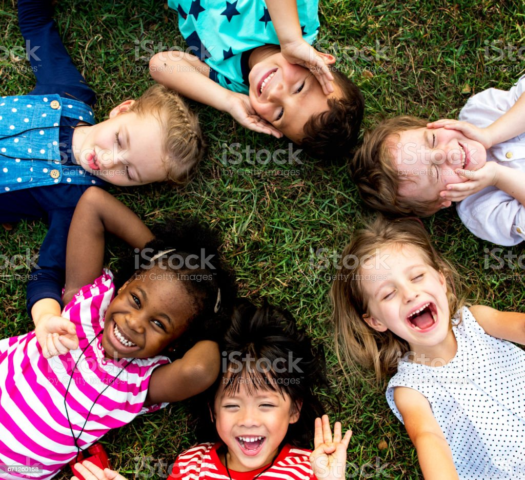 Group of kindergarten kids lying on the grass at park and relax with smiling stock photo