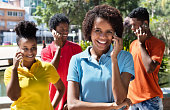 Group of latin american young adult talking at phone