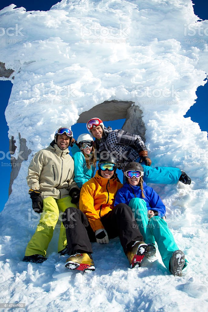 Group of laughing skiers and snowboarders posing for photo. stock photo